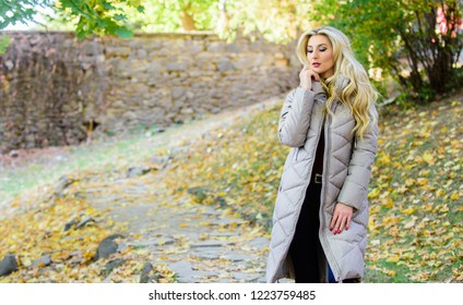 Puffer jacket casual and comfortable style. Girl fashionable blonde walk in autumn park. Woman wear warm grey jacket. Jacket everyone should have. Puffer fashion trend concept. Oversized jacket trend.