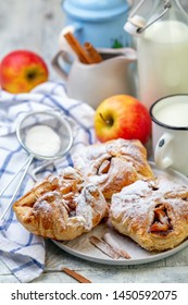 Puffs of apples and cinnamon on a plate sprinkled with powdered sugar, selective focus.