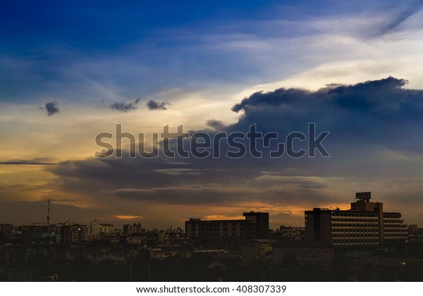 Puffy band of dark clouds over silhouettes of buildings at sunset in Bangkok, Thailand.