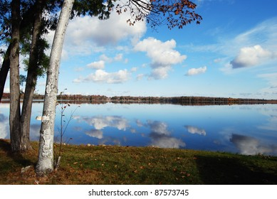 Puffy cloud filled blue sky over tranquil lake in Minnesota