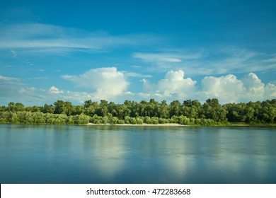 The puffy clouds above forest and river (lake). Wide angle
