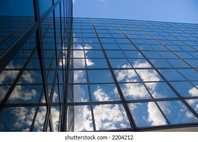 Puffy white clouds reflected in glass of an office building - and then reflected back onto a 90 degree facing wall of windows.