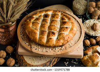Puffy,ramadan bread on the round,wood tray with wheat grains.Conceptual design.