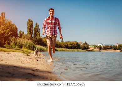 Pug dog playing with master by river. Happy puppy running and having fun. Dog pursueing man outdoors