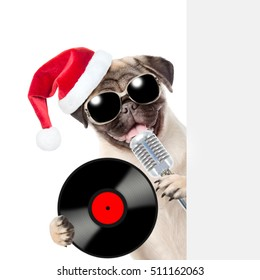 Pug puppy with retro microphone with vinyl record in red santa hat peeking from behind empty board. isolated on white background