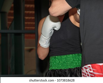 Pugilist Girl at Boxing Training in the Ring with Sparring Partner.
