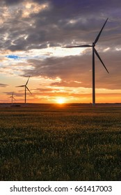 Puglia (Italy) - Wind farm with rock ruins, wind turbines and bales of hay at sunset
