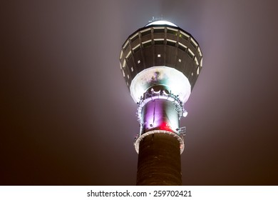 Puijo outlook tower in night lighting against evening sky in Kuopio, Finland