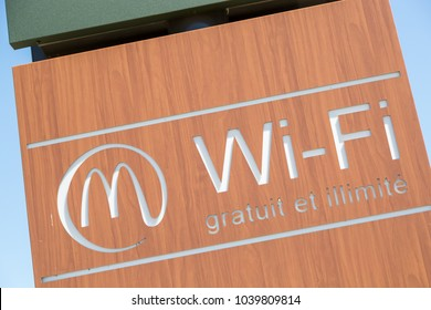 "Puilboreau, France - August 7, 2016 : McDonald's, signboard against blue sky with wifi logo and text free and unlimited (""Gratuit et illimite"" in french) on brown board"