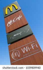 "Puilboreau, France - August 7, 2016 : McDonald's, signboard against blue sky with mccafe, mcdrive and wifi logo and text free and unlimited (""Gratuit et illimite"" in french) on brown board."