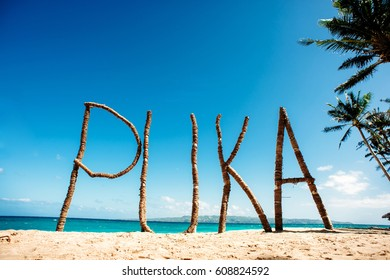 Puka Beach, Boracay, Philippines. Big wooden sign on the beach sand. Blue sky and ocean on the background.