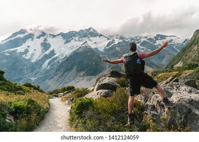 Pukaki, New Zealand - Jan 2019: Man hiker having fun at Mount Cook on the Hooker trail tramping trek. Dramatic adventure. Snow capped Mountain background. Grey cloudy moody. Shot in South Island.