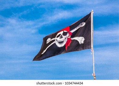 PUKET, THAILAND-FEB 2, 2016: Jolly Roger Black pirate flag with human skull on blue sky on Feb2, 2016, at Phuket, Thailand.