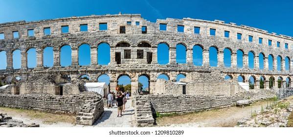 PULA, CROATIA – AUGUST 10, 2018: Tourists admire Pula Arena - ancient amphitheater located in Pula, Istria, Croatia. Panoramic photo. Travel destination. Famous object. Illustrative editorial.