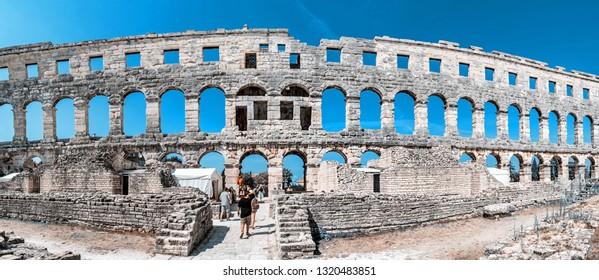 PULA, CROATIA – AUGUST 10, 2018: Tourists admire Pula Arena - ancient amphitheater located in Pula, Istria, Croatia. Panoramic photo. Teal and orange filter. Famous object. Illustrative editorial.