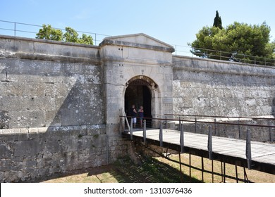PULA, CROATIA - AUGUST 16, 2017: Fortress of Pula town (also it is museum of weapon), Istria region (Adriatic seashore). View on a entry gate, ditch and bridge with tourists.