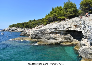 PULA, CROATIA - AUGUST 17, 2017: Grotto of Pula town, clean blue water of Adriatic sea and people relaxing on a rocky beach, Istria region