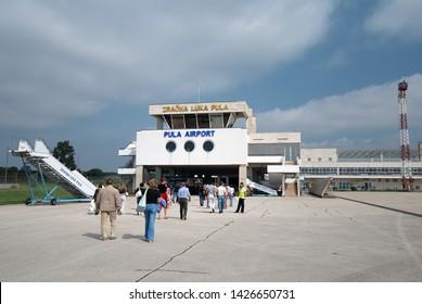 Pula, Croatia - August 29, 2007: Airport of Pula town (Istria region, Adriatic seashore), passengers moving to the terminal.
