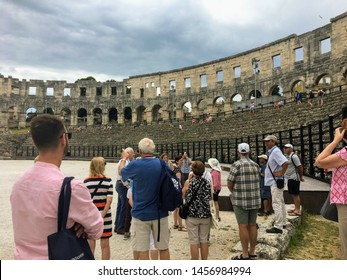 Pula, Croatia, July 4th, 2019: A group of tourists admiring the view inside the Pula Theatre in Pula, Croatia.  This amphitheatre was an ancient Roman arena for gladiator battles.