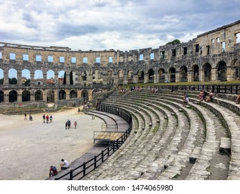 Pula, Croatia, July 4th, 2019: A wide view of a group of tourists admiring the view inside the Pula Theatre in Pula, Croatia.  This amphitheatre was an ancient Roman arena for gladiator battles.