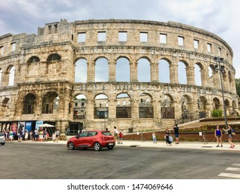 Pula, Croatia, July 4th, 2019: A full view of a group of tourists outside admiring the view of the Pula Theatre in Pula, Croatia.  This amphitheatre was an ancient Roman arena for gladiators.