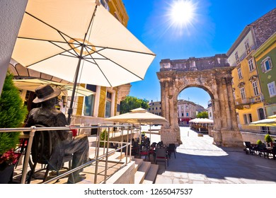 Pula, Croatia, June 26 2018: Street of Pula with historic Roman Golden gate and James Joyce statue view, Istria region of Croatia. Sculptured in bronze by Mate Čvrljak, croatian sculptor.