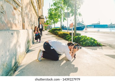 PULA, CROATIA - May 17, 2019: woman taking picture on phone like man taking picture on professional camera. street shooting