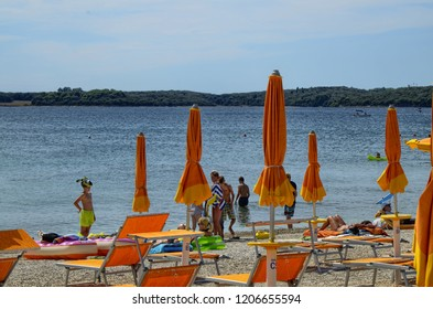 Pula, Istria, Croatia, August 2018. The beach Vile Stinjan, Puntizela. It is a beach with fine gravel, very clean with crystal clear waters. The bathing establishments have brightly colored umbrellas