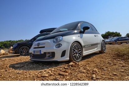 Pula, Istria, Croatia. August 2018. In the parking lot of the Kamenjak Nature Park, a Fiat 500 Abarth. The dirt road and the wild environment enhance the sporting line of the car.