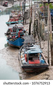 PULAU KETAM, MALAYSIA - 26 JUNE 2017 : Civilian fishing boats lying on the river bank after sea level retreated at Crab island, a famous fishing village in Malaysia.