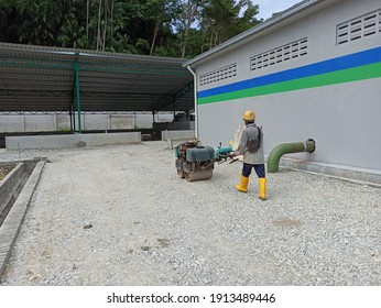 Pulau Pangkor, Perak, Malaysia - 4 January 2021. Worker compacting subbase for premix road in construction site.