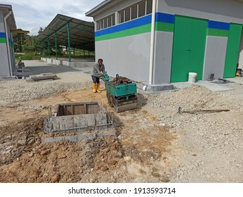 Pulau Pangkor, Perak, Malaysia. 8 January 2021. Worker compacting subbase for premix road in construction site.
