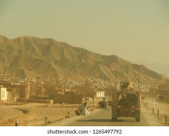 PULI KHUMRI, AFGHANISTAN, MAR 21, 2011: American military convoy travels through the town of Puli Khumri Afghanistan in Baghlan Province.