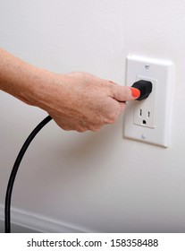 pull the plug concept with woman pulling black cord and plug