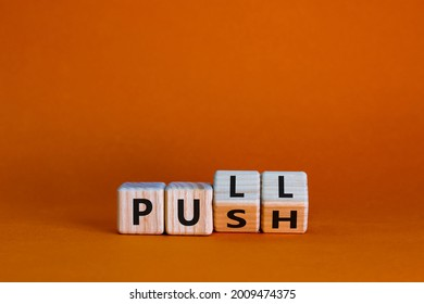 Pull or push symbol. Turned wooden cubes and changed the word 'push' to 'pull'. Beautiful orange background, copy space. Business and pull or push concept.