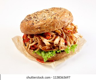 Pulled chicken kebab burger with spicy chili and lettuce on a healthy wholewheat bun over a white background