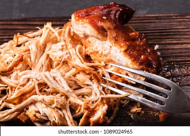 Pulled chicken on a wooden kitchen board with a fork.Close-up