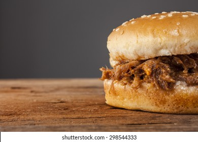 Pulled pork in a bun shot front on on wood with grey background