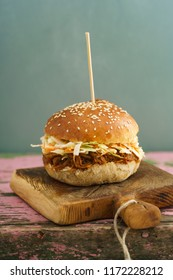 Pulled pork burger with homemade burger bun, pulled pork and coleslaw on wooden board