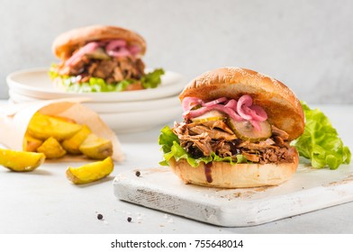 Pulled pork burger with pickles on light wooden background