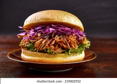 Pulled pork burger with red cabbage salad and bbq sauce on plate with dark background