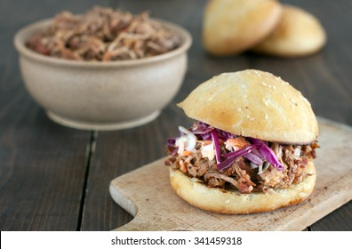 Pulled pork burger with red cabbage salad and bbq sauce in a homemade bun