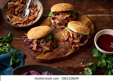 Pulled pork burgers with pickled and fresh vegetables and coriander on brown wooden background - Shutterstock ID 1861128649