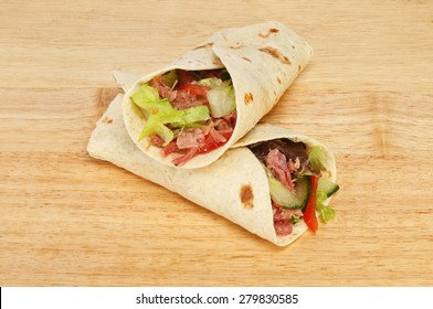 Pulled pork and salad bread wraps on a wooden board
