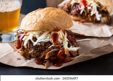 Pulled pork sandwich with cabbage slaw on top served on paper