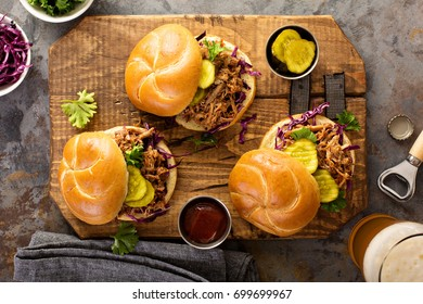 Pulled pork sandwiches with BBQ sauce, cabbage and pickles overhead shot