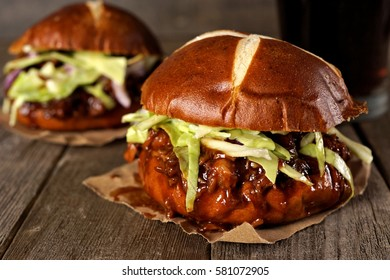 Pulled pork sandwiches on pretzel buns against a rustic wood background