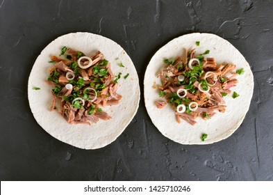 Pulled pork soft tacos on black stone background. Top view, flat lay