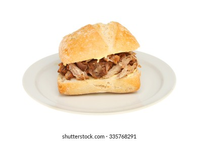 Pulled pork in a sourdough bread roll on a plate isolated against white