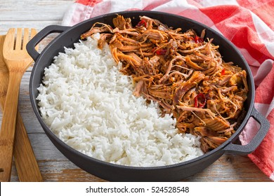 pulled slow-cooked pork shoulder grilled in oven with long-grain basmati rice in iron stewpot with kitchen towel, on wooden table, view from above, close-up